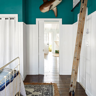 Inspiration for a small beach style loft-style bedroom in New York with blue walls, dark hardwood floors and brown floor.