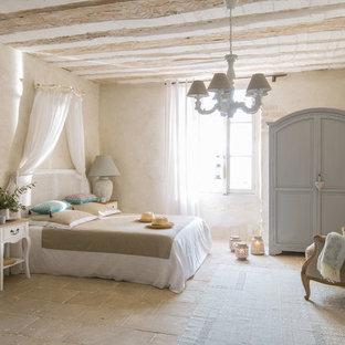 Идея дизайна: спальня среднего размера в средиземноморском стиле с бежевыми стенами, полом из травертина, стандартным камином, фасадом камина из кирпича и бежевым полом