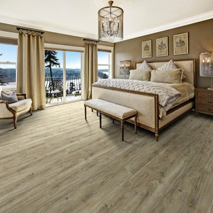 Photo of a large traditional master bedroom in Los Angeles with brown walls, vinyl floors, no fireplace and brown floor.
