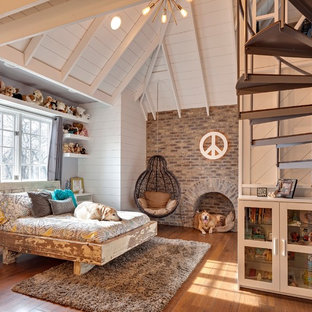 Inspiration för ett lantligt sovrum, med vita väggar, mellanmörkt trägolv och en spiselkrans i tegelsten