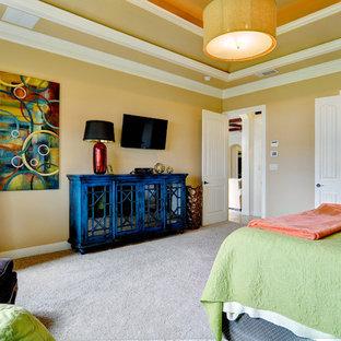 Imagen de dormitorio principal, clásico renovado, de tamaño medio, con moqueta, marco de chimenea de baldosas y/o azulejos y paredes amarillas