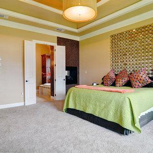 Ejemplo de dormitorio principal, clásico renovado, de tamaño medio, con paredes amarillas, moqueta, chimenea de esquina y marco de chimenea de baldosas y/o azulejos