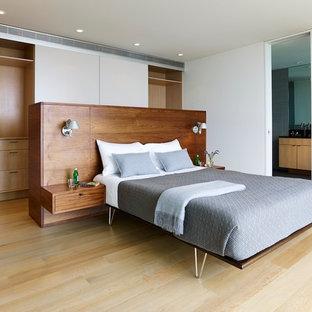 Modelo de dormitorio principal, minimalista, con paredes blancas y suelo de madera clara