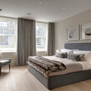 Diseño de dormitorio clásico renovado con paredes beige y suelo de madera clara