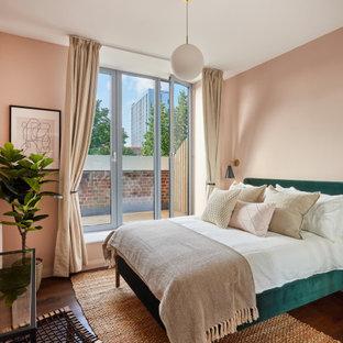 Foto de dormitorio contemporáneo con paredes rosas, suelo de madera oscura y suelo marrón
