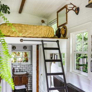 Landhaus Schlafzimmer im Loft-Style mit weißer Wandfarbe, dunklem Holzboden und braunem Boden in Portland