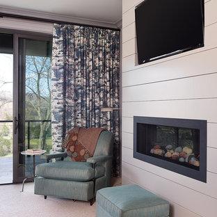 Ejemplo de dormitorio principal, tradicional renovado, de tamaño medio, con paredes beige, moqueta, chimeneas suspendidas y marco de chimenea de madera