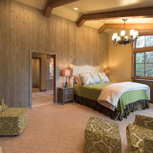 Modelo de dormitorio principal, rural, grande, con paredes beige, moqueta, chimenea tradicional y marco de chimenea de madera