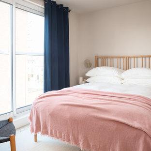 Photo of a scandinavian guest bedroom in London with beige walls, light hardwood flooring and beige floors.