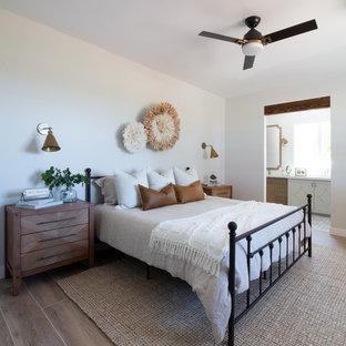 Ejemplo de dormitorio principal, campestre, de tamaño medio, con paredes blancas, suelo de baldosas de porcelana, chimenea de esquina, marco de chimenea de ladrillo y suelo beige