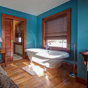 Modelo de dormitorio principal, de estilo americano, de tamaño medio, con paredes azules, suelo de madera en tonos medios, chimenea tradicional, marco de chimenea de baldosas y/o azulejos y suelo marrón