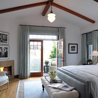 Modelo de dormitorio clásico renovado con paredes blancas, suelo de madera en tonos medios y chimenea de esquina