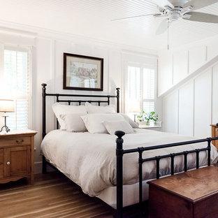 Foto på ett amerikanskt huvudsovrum, med vita väggar, mellanmörkt trägolv och brunt golv