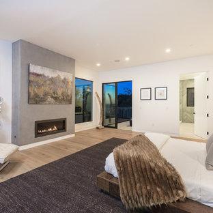 Idee per una grande camera matrimoniale moderna con pareti bianche, parquet chiaro, camino lineare Ribbon e cornice del camino in cemento