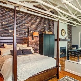 Imagen de dormitorio tipo loft, tradicional renovado, de tamaño medio, con paredes rojas, suelo de madera en tonos medios, chimenea tradicional y marco de chimenea de yeso