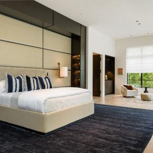 Modelo de dormitorio principal, retro, grande, con paredes beige, suelo de madera clara, chimenea lineal, marco de chimenea de piedra y suelo beige