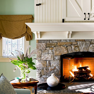 Idee per una camera da letto tradizionale con pareti verdi, cornice del camino in pietra e camino classico
