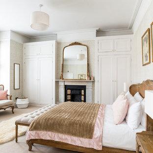 Ispirazione per una grande camera da letto tradizionale con pareti grigie, moquette, camino classico e pavimento beige