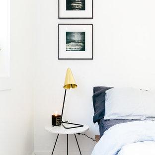 Cette image montre une petit chambre d'amis nordique avec un mur blanc et un sol en bois peint.
