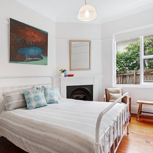 Design ideas for a transitional bedroom in Sydney with white walls, medium hardwood floors, a standard fireplace and brown floor.