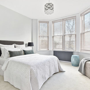Photo of a bedroom in London with grey walls, carpet and beige floors.