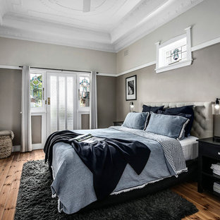 Design ideas for a mid-sized contemporary master bedroom in Sydney with medium hardwood floors, brown floor and grey walls.