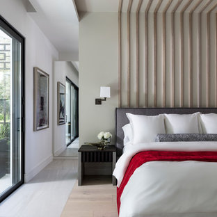 Idee per una camera da letto design con pareti verdi, parquet chiaro e pavimento beige