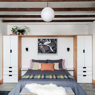 Modelo de habitación de invitados contemporánea, pequeña, con paredes blancas, suelo de cemento y suelo gris