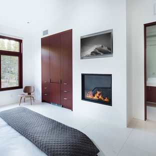 На фото: большая хозяйская спальня в современном стиле с белыми стенами, стандартным камином, фасадом камина из штукатурки и белым полом с