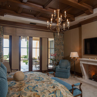 Example of a tuscan master carpeted and gray floor bedroom design in Orange County with beige walls, a standard fireplace and a stone fireplace