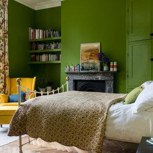 Inspiration för klassiska sovrum, med gröna väggar, en spiselkrans i sten, ljust trägolv, en standard öppen spis och beiget golv