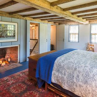 Ispirazione per una camera matrimoniale country con pareti blu, pavimento in legno verniciato, camino classico e cornice del camino in legno