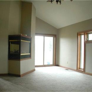 Ejemplo de dormitorio grande con paredes blancas, moqueta, chimenea de esquina y marco de chimenea de metal