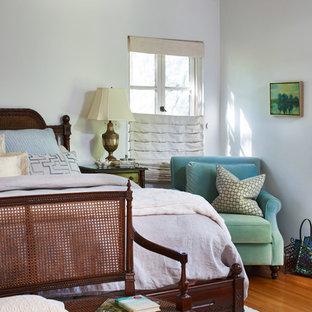 Immagine di una camera matrimoniale chic con pareti bianche, pavimento in legno massello medio e pavimento arancione
