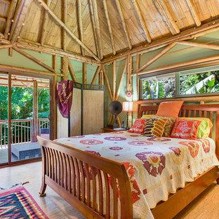 Imagen de habitación de invitados tropical con paredes verdes y suelo de bambú