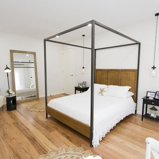 Photo of a beach style bedroom in Melbourne with white walls, medium hardwood floors and no fireplace.