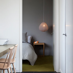 This is an example of a midcentury bedroom in Melbourne with grey walls, carpet and green floor.