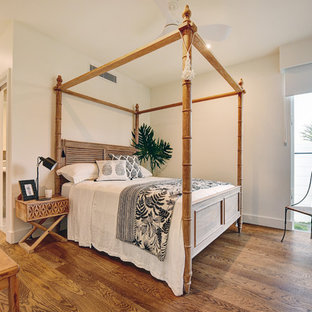Photo of a tropical bedroom in Other with white walls, medium hardwood floors and brown floor.