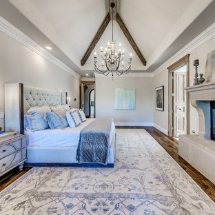 Example of a large transitional master medium tone wood floor and brown floor bedroom design in Oklahoma City with gray walls, a standard fireplace and a concrete fireplace
