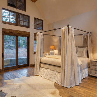 Inspiration for a rustic dark wood floor and brown floor bedroom remodel in Other with beige walls