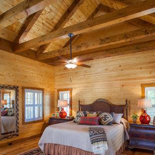 Modelo de dormitorio principal, rústico, grande, con paredes beige, suelo de baldosas de cerámica, chimenea tradicional, marco de chimenea de piedra y suelo beige