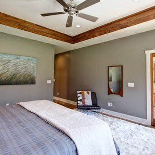Mid-sized minimalist master medium tone wood floor bedroom photo in Other with gray walls