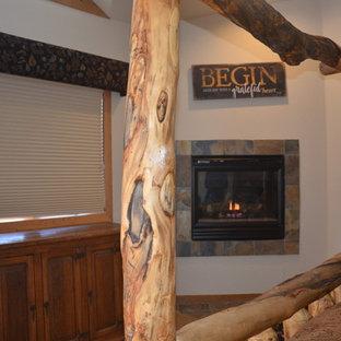 Ejemplo de dormitorio principal, rural, de tamaño medio, con paredes blancas, suelo de pizarra, chimenea tradicional, marco de chimenea de baldosas y/o azulejos y suelo gris