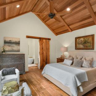 Großes Landhaus Hauptschlafzimmer mit weißer Wandfarbe, braunem Holzboden und Holzdecke in Atlanta