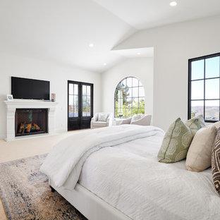 Medelhavsstil inredning av ett mellanstort huvudsovrum, med vita väggar, heltäckningsmatta, en standard öppen spis, en spiselkrans i betong och beiget golv