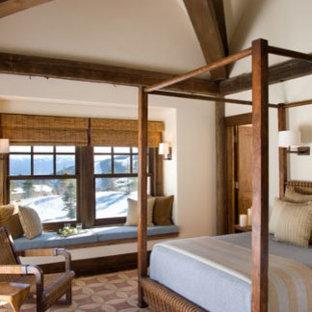 Modelo de dormitorio principal, rústico, extra grande, con paredes beige, suelo de bambú, chimenea tradicional y marco de chimenea de piedra