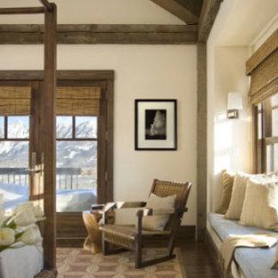 Modelo de dormitorio principal, rural, grande, con paredes beige, suelo de madera oscura, chimenea tradicional y marco de chimenea de piedra