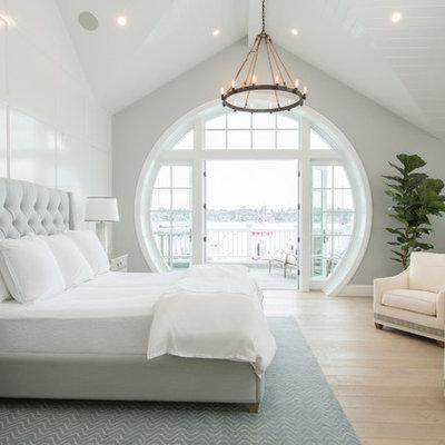 Example of a beach style light wood floor and beige floor bedroom design in Orange County with blue walls