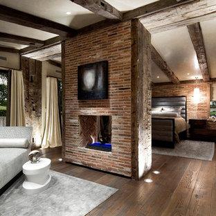 Diseño de dormitorio principal, ecléctico, grande, con paredes beige, suelo de madera oscura, chimenea de doble cara y marco de chimenea de ladrillo