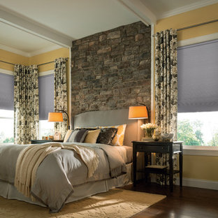 Large transitional master bedroom in Other with yellow walls, dark hardwood floors, no fireplace and brown floor.